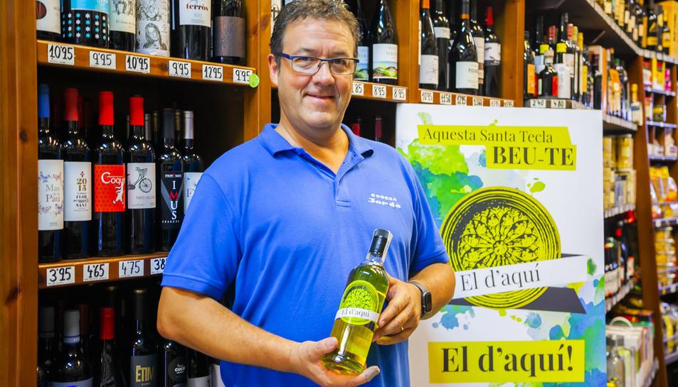 Eduard Jordà mostra una botella del licor d'herbes que ha creat amb segell tarragoní.