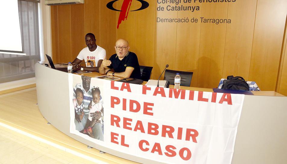 Ibrahima Sylla i de l'advocat Ramon Setó en roda de premsa a Tarragona, amb una pancarta per demanar la reobertura del cas per la mort d'un manter a Salou l'agost del 2015.