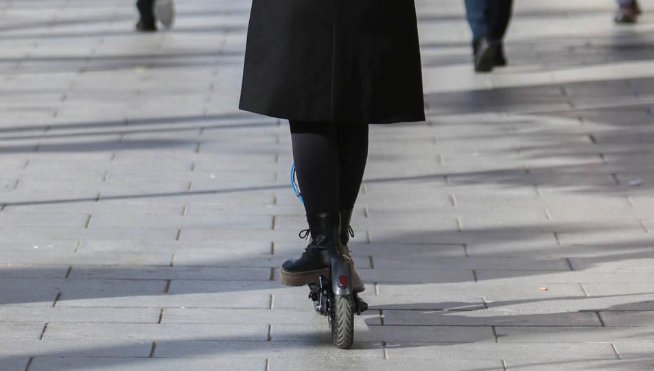 Una dona circulant en patinet elèctric.
