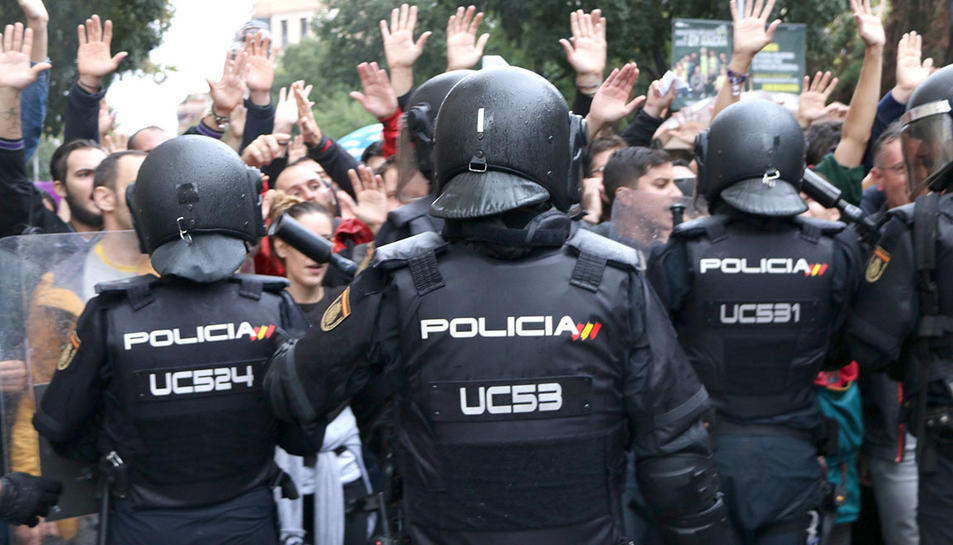 agents de la policia espanyola d'esquenes intentant impedir el pas de ciutadans que feien cua per votar a l'Escola Ramon Llull, l'1 d'octubre de 2017