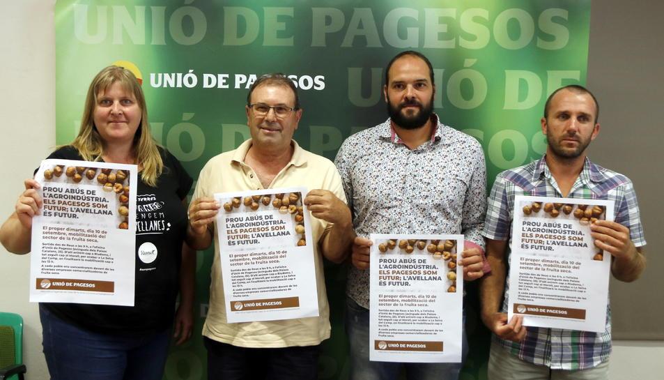 Pla mitjà del responsable nacional de la fruita seca d'Unió de Pagesos, Rafel Español (el segon per l'esquerra), mostrant els cartells de la protesta de dimarts juntament amb altres membres del sindicat a Reus, el 6 de setembre del 2019