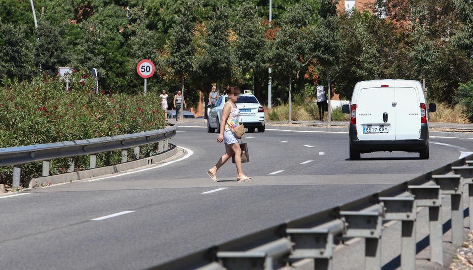 Alguns vianants passen per Bellissens esquivant els cotxes.