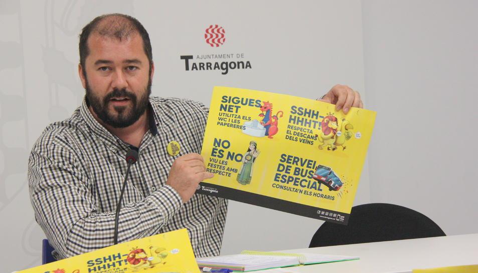 El portaveu de l'Ajuntament de Tarragona, Xavier Puig, sostenint el cartell que apel·la al civisme dels ciutadans durant les festes de Santa Tecla.