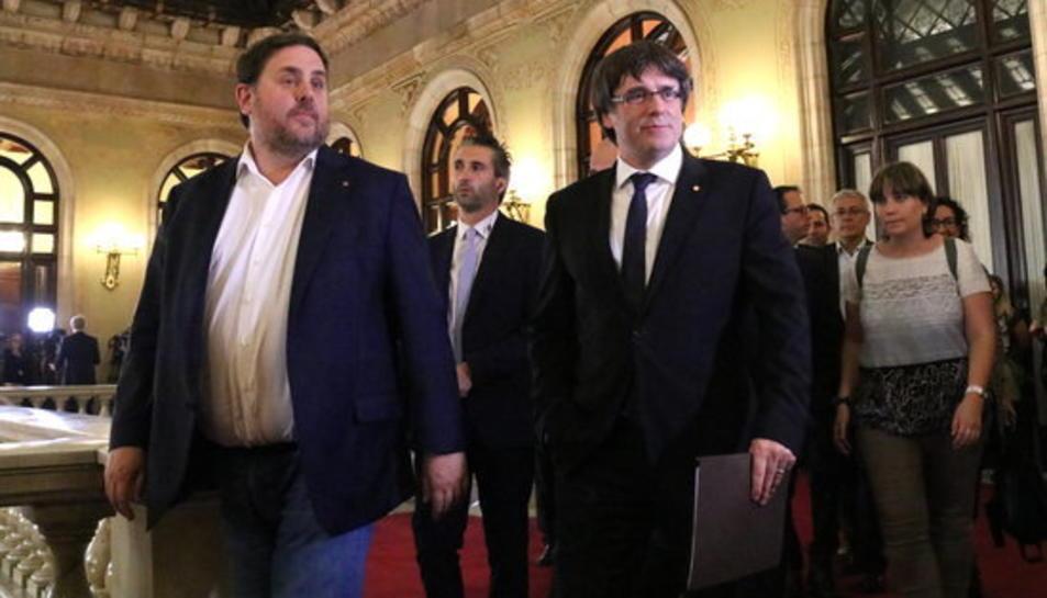 Imatge d'arxiu de l'expresident i l'exvicepresident de la Generalitat, Carles Puigdemont i Oriol Junqueras, dirigint-se a l'hemicicle.