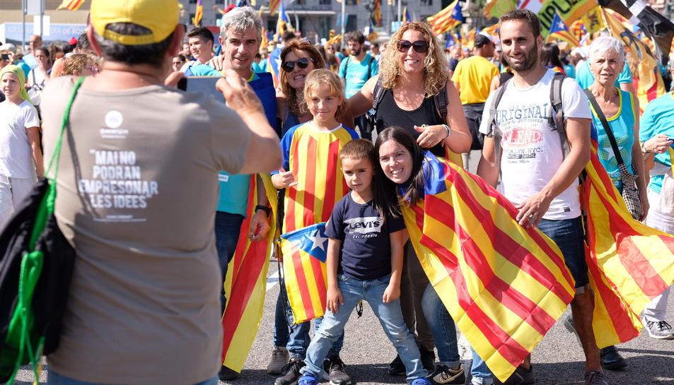 Famílies es fan fotografies a la manifestació de la Diada a la plaça d'Espanya.
