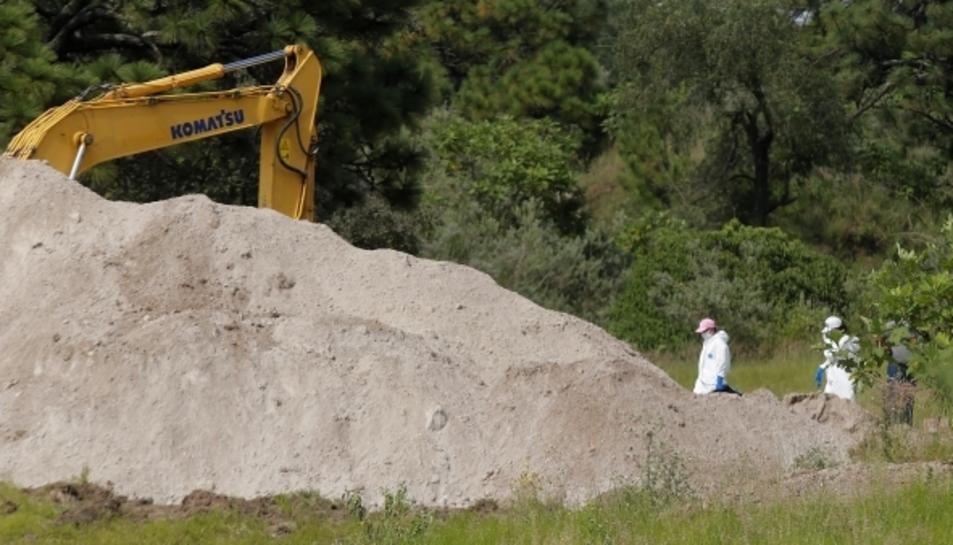 Perits forenses treballant en la fossa clandestina al costat de maquinària pesada.