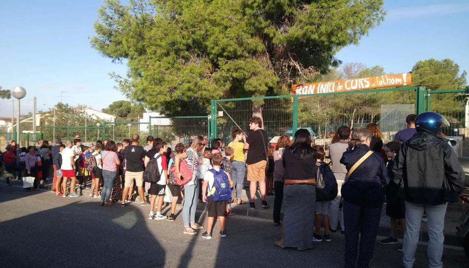 Imatge de diversos alumnes i els seus pares davant l'Escola l'Arrabassada el primer dia del curs 2019-202.