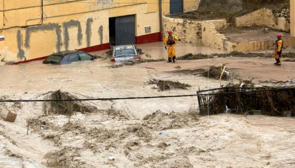 Membres de l'equip de rescat inspeccionen aquest dijous Ontinyent on el riu Clariano s'ha desbordat.