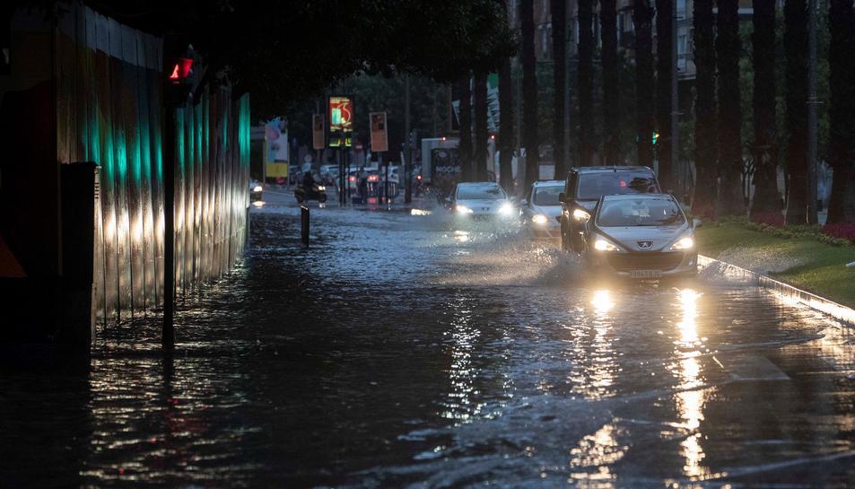 Diversos cotxes circulen aquest matí pel carrer Plano de San Francisco de Múrcia, inundada després de les intenses pluges caigudes aquesta matinada.