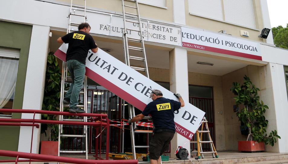 Dos operaris instal·lant el nou rètol de la Facultat de Ciències de l'Educació i Psicologia de la URV.