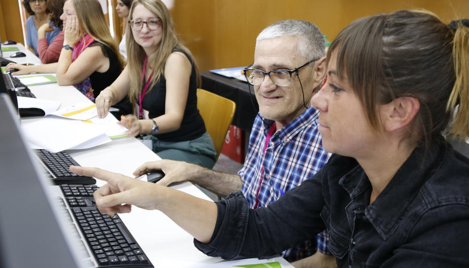 Un home gran aprenent com funciona una nova plataforma digital, en una prova pilot d'àmbit europeu a la URV.