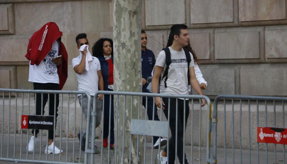 Pla general de tres dels acusats, acompanyats d'una familiar, arribant a l'Audiència de Barcelona.