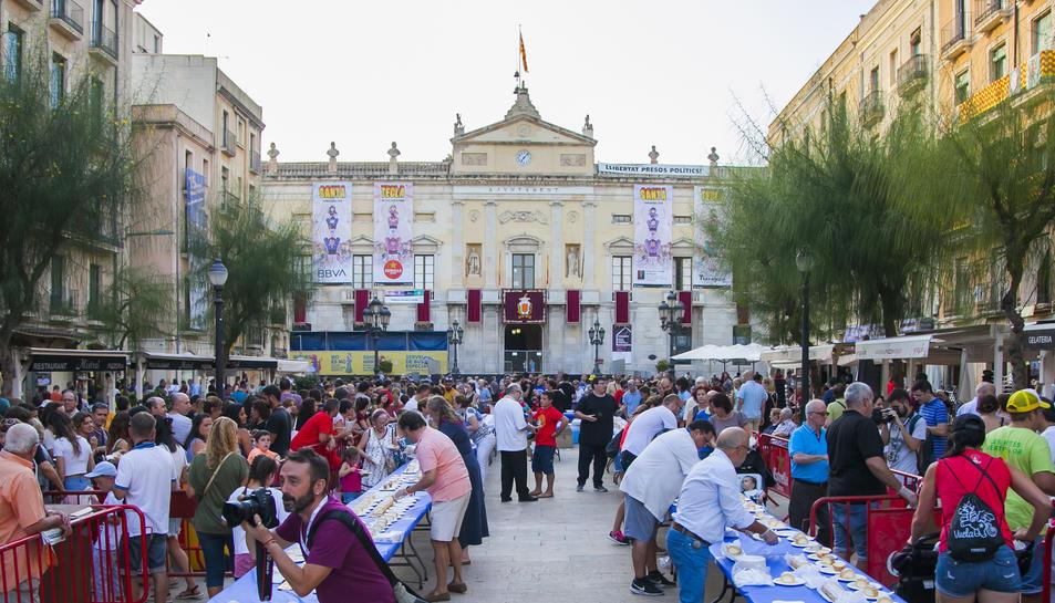 Centenars de persones van fer cua a la plaça de la Font per poder degustar el pastís.
