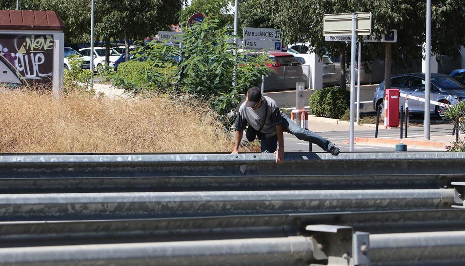 Un home passa la mitgera que separa els quatre carrils.