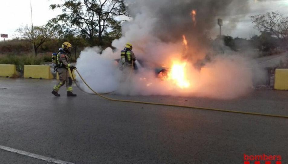 Dos bombers extingitn el foc del vehicle.