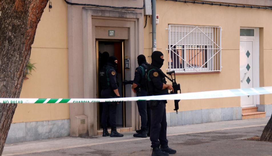 Diversos agents de la Guàrdia Civil a la porta d'un habitatge del carrer Goya de Sabadell on estan duent a terme un escorcoll.