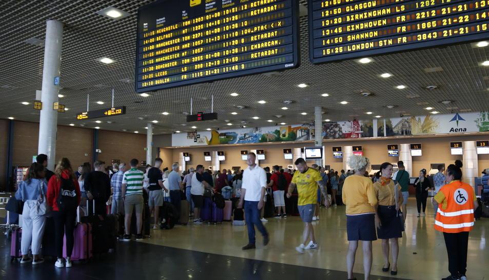 Pla general de cues per facturar a l'Aeroport de Reus i del panell informatiu que indica retards en els vols amb destinació al Regne Unit que operava la companyia Thomas Cook. Imatge del 24 de setembre del 2019. (Horitzontal) Vincular  Crear
