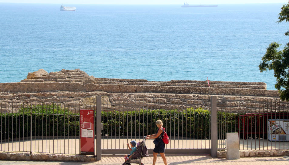 Pla general d'una dona passant amb el carret d'un nadó per davant de la reixa de l'amfiteatre romà de Tarragona, tancat al públic de forma provisional. Imatge del 27 de setembre del 2019