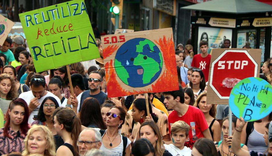 Pla tancat de diversos manifestants alçant cartells amb motiu de la manifestació sobre l'emergència climàtica a Tarragona, el 27 de setembre del 2019