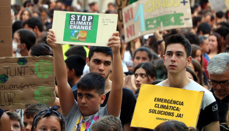 Pla mitjà d'un nen i un noi mostrant cartells contra el canvi climàtic a la plaça de la Font de Tarragona, el 27 de setembre del 2019