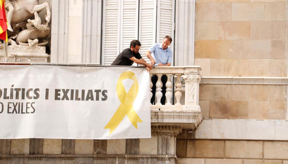 Dos treballadors comencen a treure la pancarta dels presos del Palau de la Generalitat.