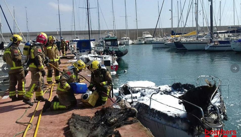 Bombers actuant al port de Torredembarra davant l'embarcació que ha cremat.
