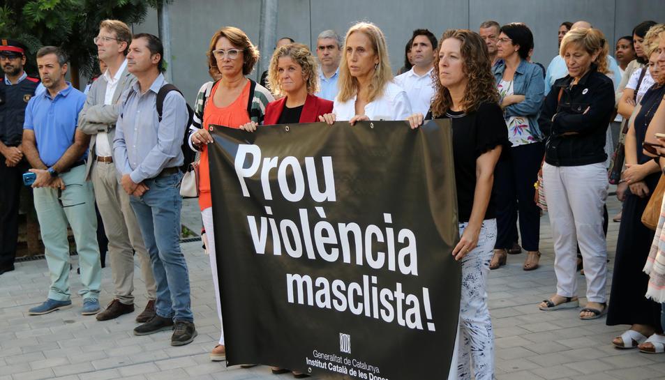 Pla general de les persones concentrades i la pancarta desplegada durant el minut de silenci per recordar la dona morta a mans del seu fill el passat divendres a Tortosa.