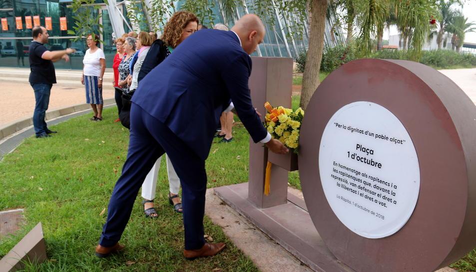 Pla general de l'alcalde de Sant Carles de la Ràpita, Josep Caparrós, dipositant un ram de flors al monument commemoratiu de l'1-O. Imatge de l'1 d'octubre de 2019