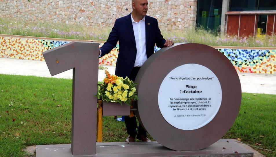 Pla conjunt de l'alcalde de la Ràpita, Josep Caparrós, darrere del monument que recorda els fets de 1-O al municipi. Imatge de l'1 d'octubre de 2019