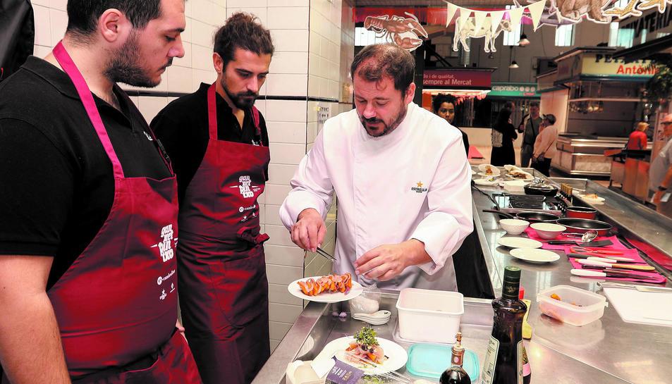 Un dels xefs convidats donant consells a dos cuiners d'un dels establiments participants.