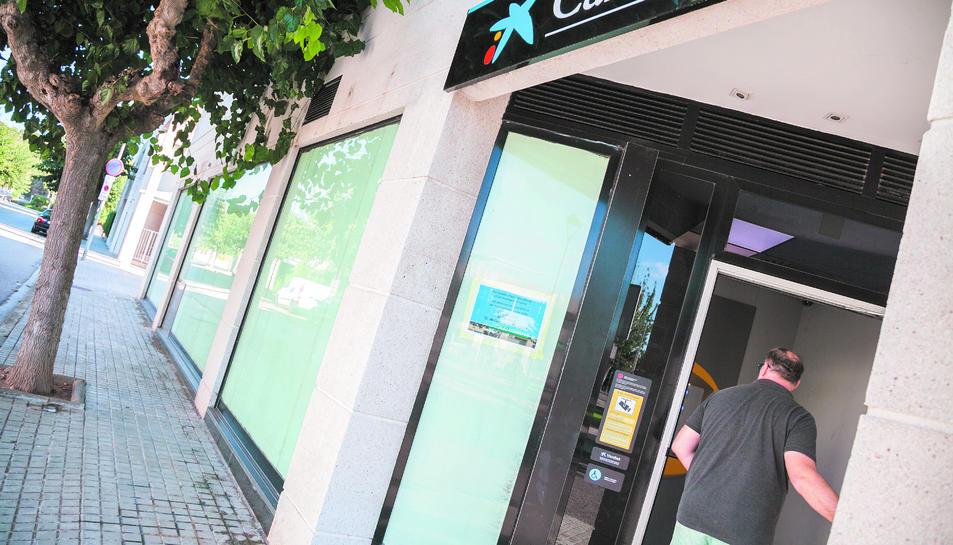 Una persona accedeix al caixer automàtic, un cop tancada l'oficina de la Móra.
