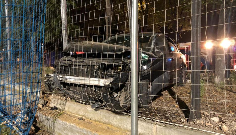 Imatge del cotxe encastat contra un petit mur i la xarxa del camp.