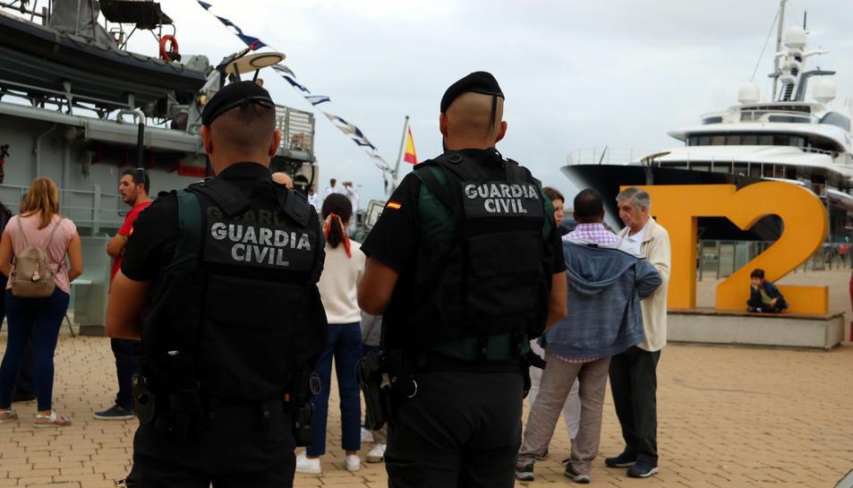 Pla obert de dos agents de la Guàrdia Civil d'esquenes fent tasques de vigilància del patruller Infanta Cristina ubicat al Moll de la Costa del Port de Tarragona. Imatge del 12 d'octubre del 2019 (Horitzontal).