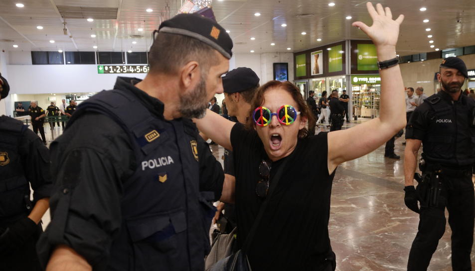 Una manifestant amb unes ulleres amb el símbol de la pau discuteix amb un agent dels Mossos quan la desallotgen.