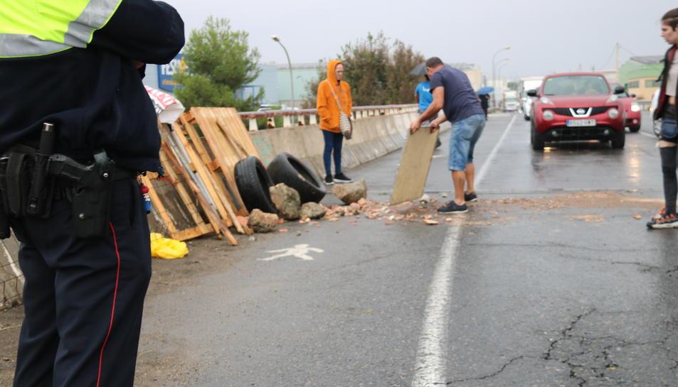 Tall a la carretera N-240 a Valls, a tocar del polígon industrial, de joves deixant runa a la calçada davant una cua de cotxes i les cames d'un mosso en primer terme, arran la sentència del judici al procés. Imatge del 14 d'octubre del 2019