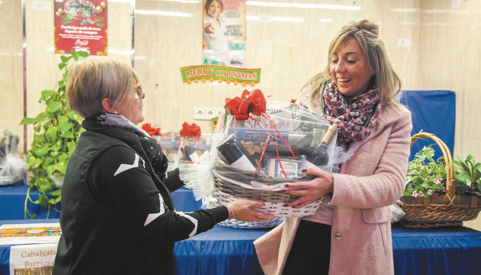 Una clienta –dreta– rep la cistella guanyadora del sorteig del Nadal passat al mercat de Torreforta.