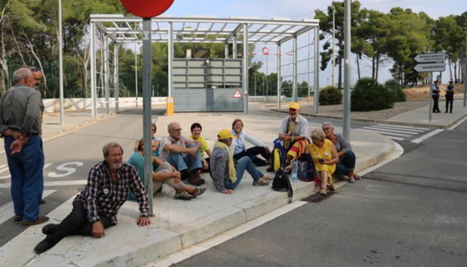 Pla obert d'un grup d'avis de Valls, asseguts davant el punt de control d'accés a la presó de Mas d'Enric al Catllar.