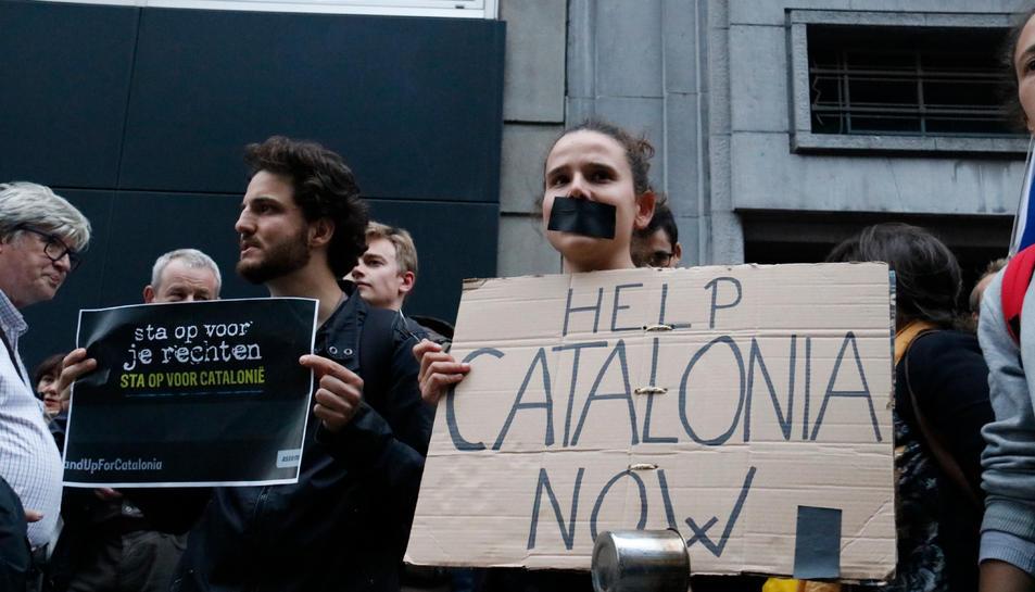 Una noia amb el cartell 'Help Catalonia now' durant la protesta davant l'ambaixada espanyola a Brussel·les.