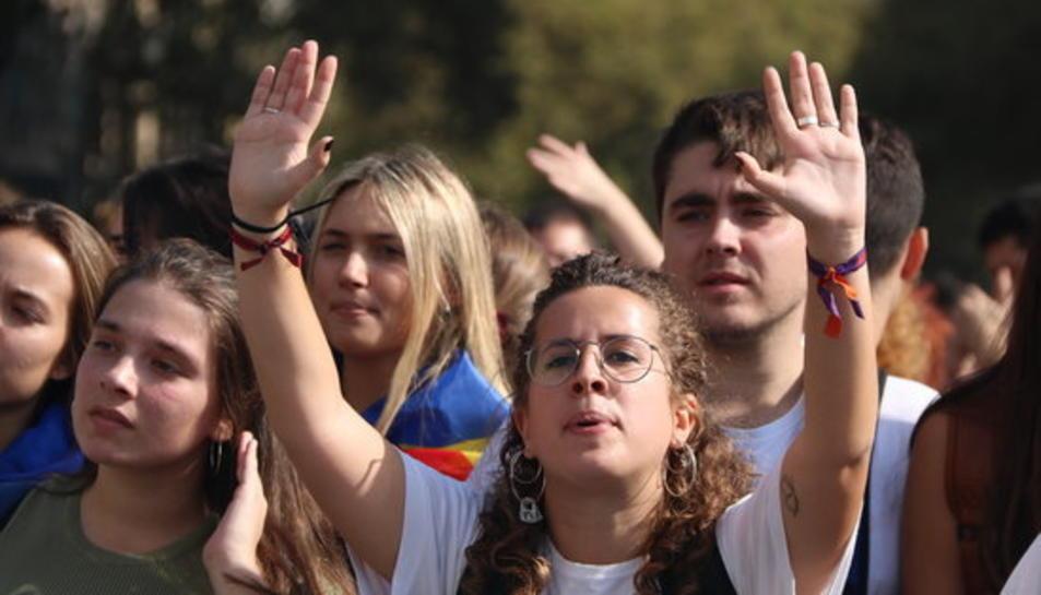 Primer pla d'una noia amb les mans aixecades durant la manifestació d'estudiants del 14 d'octubre.