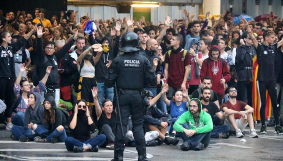 Un grup de manifestants a l'aeroport del Prat convocats per Tsunami Democràtic, darrere d'una línia policial.