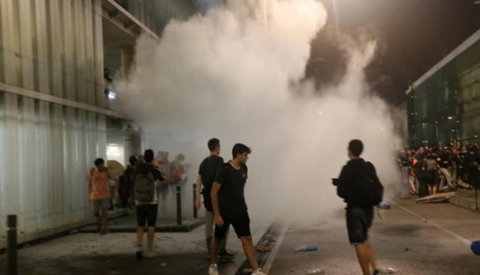 Un grup de manifestants a l'aeroport del Prat convocats per Tsunami Democràtic, enmig de fum.