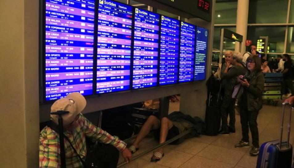Passatgers consultant els panells informatius de sortides mentre un home hi dorm a sota, a la terminal 1 de l'aeroport del Prat, l'endemà del bloqueig per part de milers de manifestants després de conèixer-se la sentència de l'1-O.
