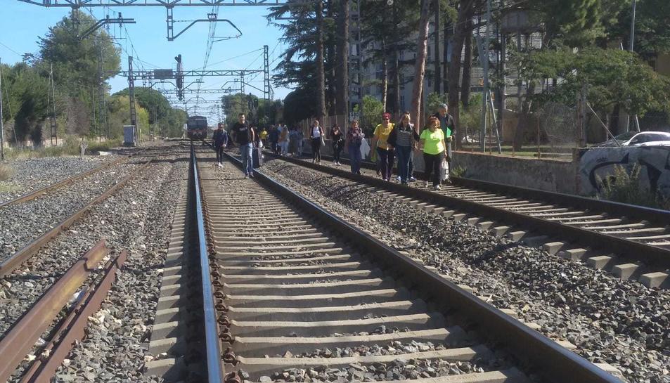 Imatge de passatgers d'un comboi aturat que han hagut de baixar abans d'arribar a l'estació i caminar per les vies.