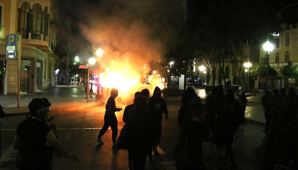 Pla genera de manifestants i contenidors cremant al fons de la Rambla Nova de Tarragona. Imatge del 16 d'octubre de 2019