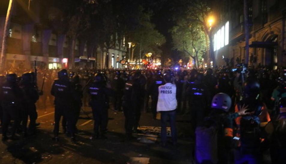 Cordó dels Mossos, en primer terme davant de la línia de manifestants, al voltant de la delegació del govern espanyol a Barcelona el 15 d'octubre.