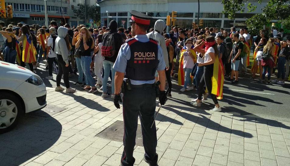 Els estudiants de Reus passen per davant dels jutjats. En primer pla, un agent dels Mossos.