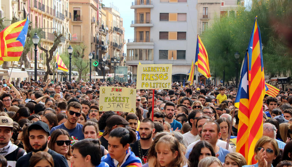 Pla mitjà de cartells reivindicatius i estelades a la plaça de la Font durant una concentració durant la jornada de vaga general el 18 d'octubre del 2019