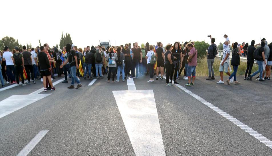 Primer pla de les senyals a l'asfalt de l'AP-7 a l'Ampolla amb els manifestants al fons. Imatge del 18 d'octubre del 2019 (vertical)
