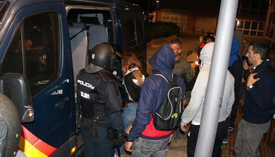 Pla general de la noia detinguda pujant a la furgoneta de la Policia Nacional, envoltada d'agents.