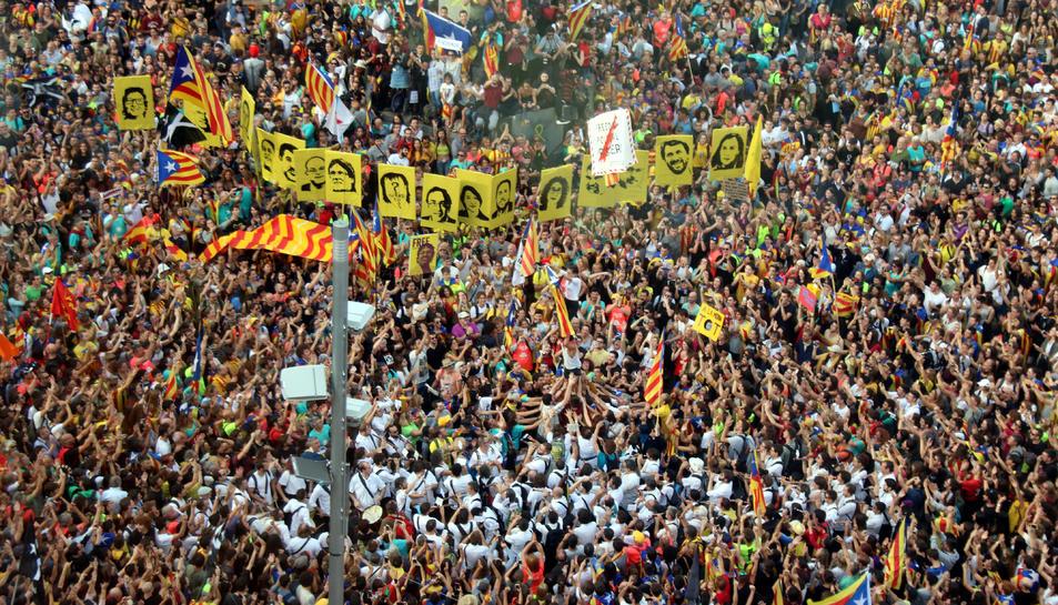 Aixequen un castell davant de les fotos dels polítics empresonats a la Plaça Cinc d'Oros.